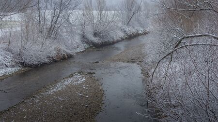 icy stream in winter with snow