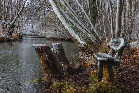 Bench at a brook in winter with snow Banco de Imagens
