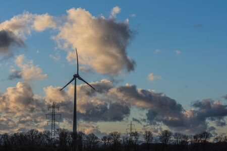 masts for electricity and wind turbines with clouds