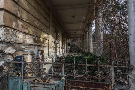 old abandoned villa with columns and garden gate