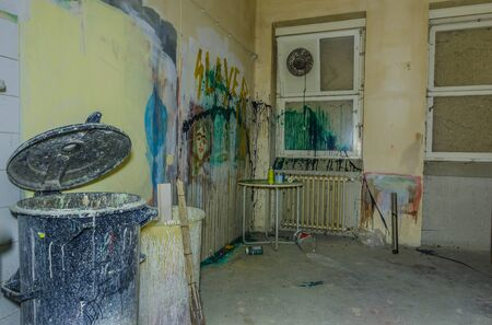 Tons of colorful paint in room of an old hospital