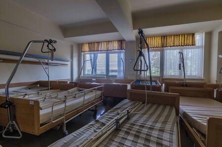 many hospital beds in large abandoned sanatorium