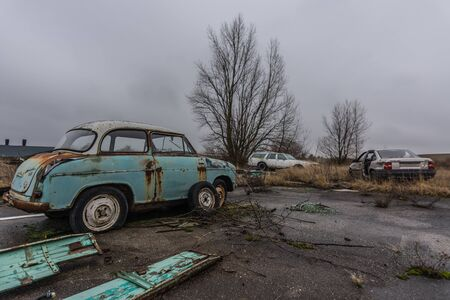 old single cars on a abandoned junkyard 版權商用圖片