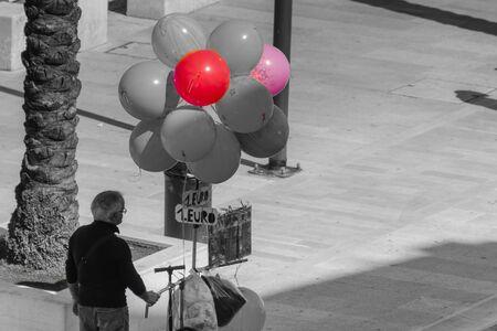 palloncini parzialmente colorati in vendita per bambini con un ambiente grigio Archivio Fotografico