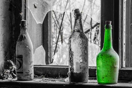 Single green bottle near a window in old house with gray background
