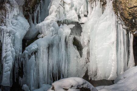 muchos carámbanos blancos en una cascada en invierno