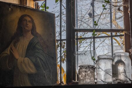 Picture of a praying woman near a window in a house