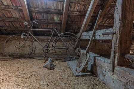 old bicycle with shovel on a loft of a house