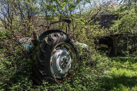 old overgrown tractor at a farm