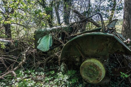 old overgrown green tractor at a farm Imagens