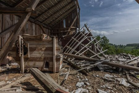 thresher in a collapsed loft with a view to the landscape
