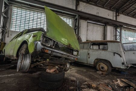 old green obliquely car in a hall of a garage Imagens