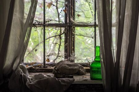 glowing green bottle on a window of an old house