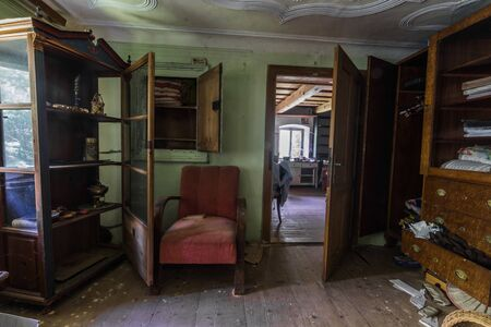 open door in a room with a display case in an abandoned house