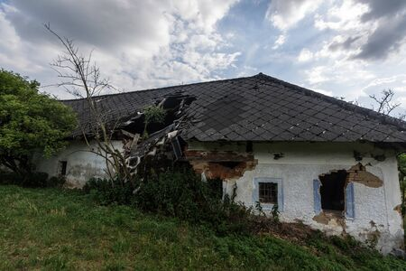 collapsed roof of an old house in the mountains with sky