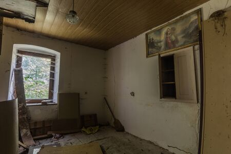 Religious picture on the wall of an old abandoned farmhouse