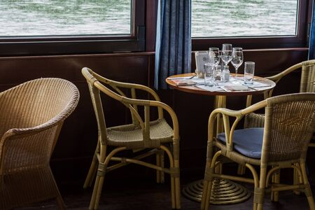 table with glasses and armchairs on a ship on a river Reklamní fotografie