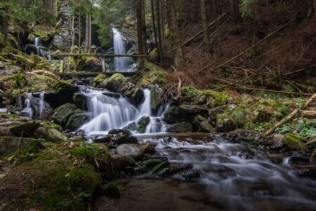 beautiful flowing waterfall with a bridge in the forest while hiking