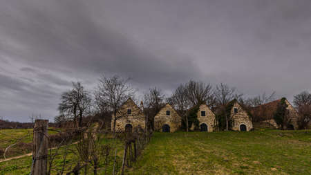 houses made of stone in a vine landscape with dark sky Imagens