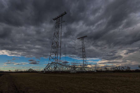 high antenna and dark rainclouds in a flat landscape 版權商用圖片