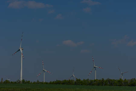 wind turbines in a nature landscape with sky and green field