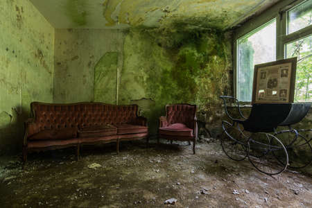 stroller and red sofa in a moldy green room