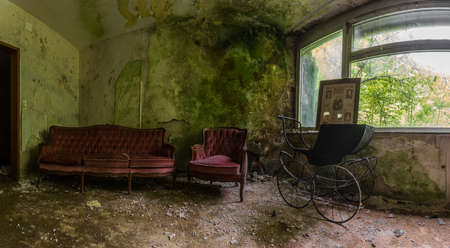 stroller and red sofa in a green room panorama view Archivio Fotografico