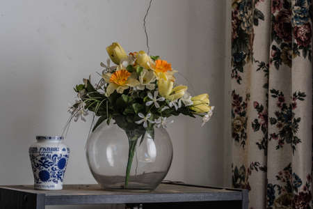 ceramic jar vase made of glass and plastic flowers in a old house