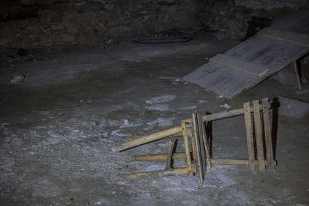 broken lying wooden chair in a castle cellar Archivio Fotografico