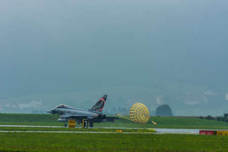 jet with yellow parachute while landing in fog on a air show