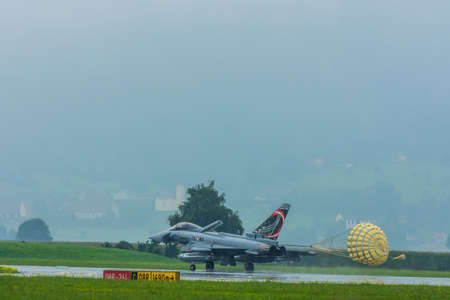 jet with parachute on landing at a air show in the mountains Stok Fotoğraf