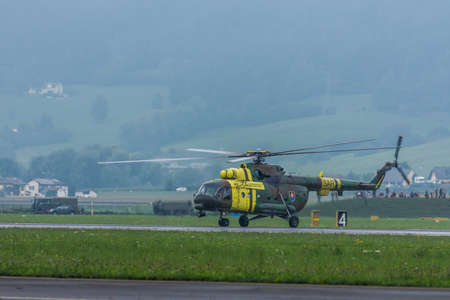landed military helicopter with green and yellow color at a air show
