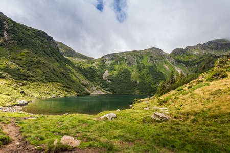 green nature landscape with mountain lake while hiking in the summer