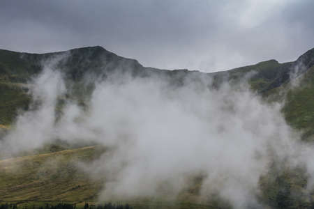 dense white raincloud while hiking in the mountains in the summer Zdjęcie Seryjne