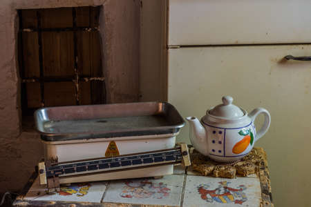 old scale and a teapot on a table in a abandoned house