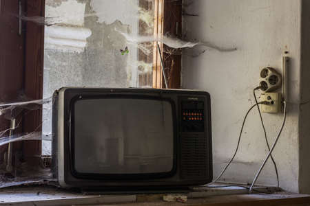 old television on a windowsill with cobwebs in a abandoned house Archivio Fotografico