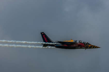 colorful jet plane from red bull at a air show with rain