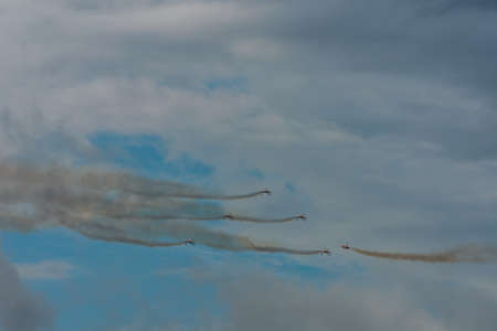 five planes with smoke fly against each other on the sky with clouds at a air show
