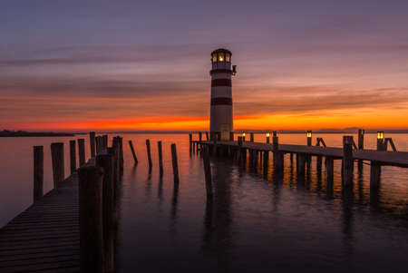 wooden jetties with lighthouse while sunset at the lake in the spring