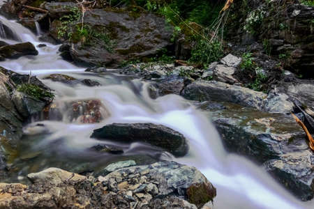 flowing soft torrent in rocky mountains near a waterfall while hiking