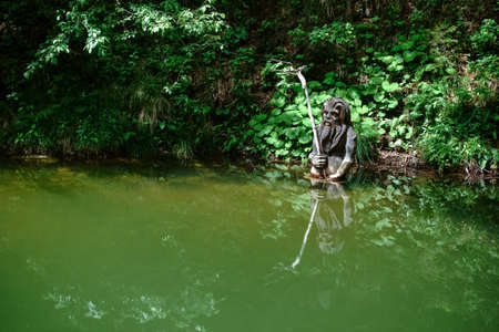 figure waterman in the green water from a pond in the forest