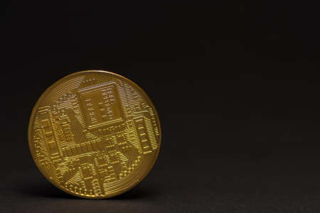 back side from a golden valuable bitcoin with black background left view 写真素材