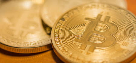 gold shiny bitcoins lying on a orange background detail panorama view 写真素材
