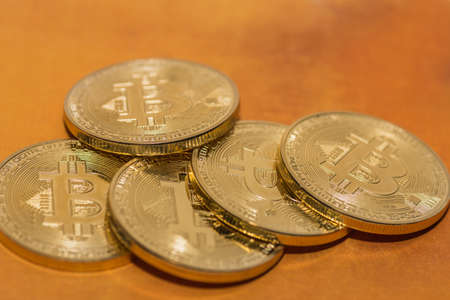 valuable bitcoins lie on top of each other on a golden background 写真素材
