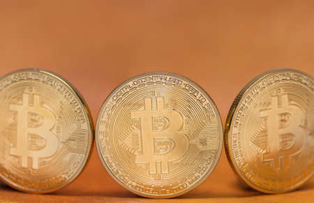 three valuable bitcoins standing in a row with orange background 写真素材