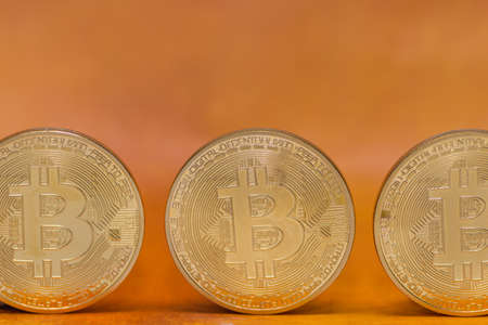 three valuable bitcoins standing on a golden background front view
