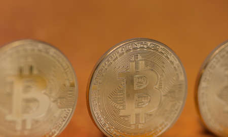 three valuable bitcoins standing with a orange background front view