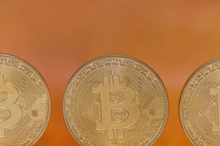 three bitcoins front view with orange background macro view
