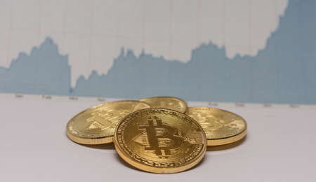 lying bitcoins with a fluctuating stock market chart middle view