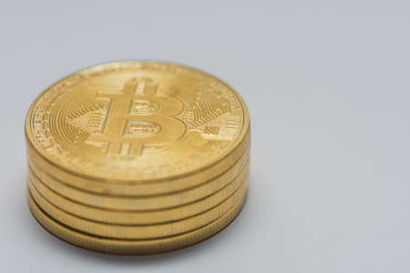 stacked bitcoins standing on a gray background left bottom view